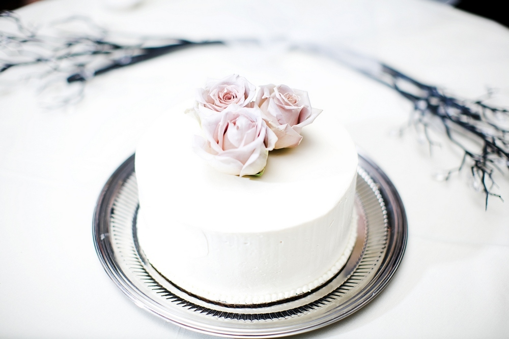 Mini white wedding cake on silver tray with blush pink roses on top