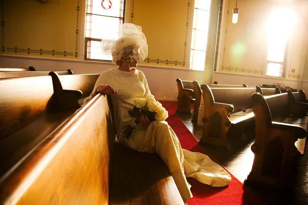 Vintage-chic bride sits in ceremony church, waiting to say I Do