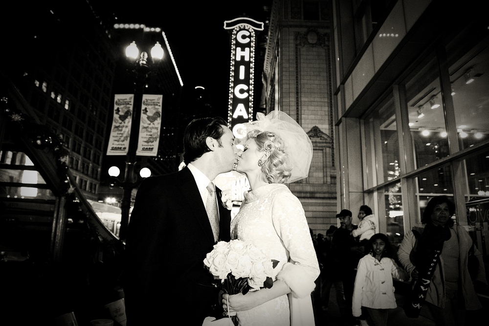 Vintage-bride-and-groom-downtown-chicago-wedding-kiss-beneath-chicago-theatre-sign.full