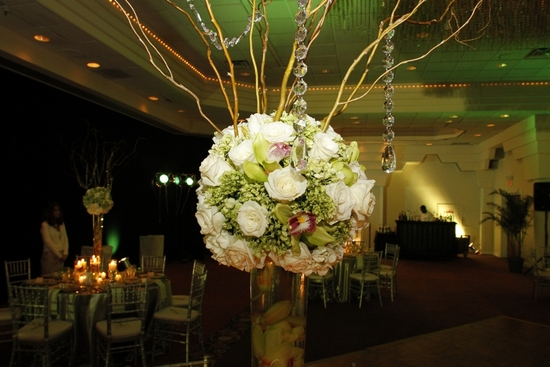 Ivory roses, and green with a touch of fuchsia orchids arranged in a dome shape for the topiari tabl