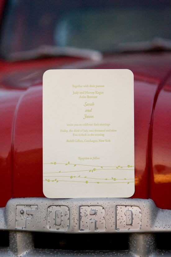 This cream wedding invitation with sage green writing is being displayed on an old car.