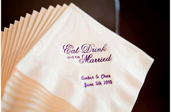 White cocktail napkins adorned with cursive purple writing- Eat, Drink, Be Married