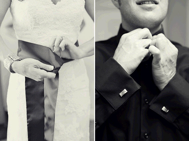 Bride ties the black sash on her ivory lace wedding dress; groom buttons up black tux shirt
