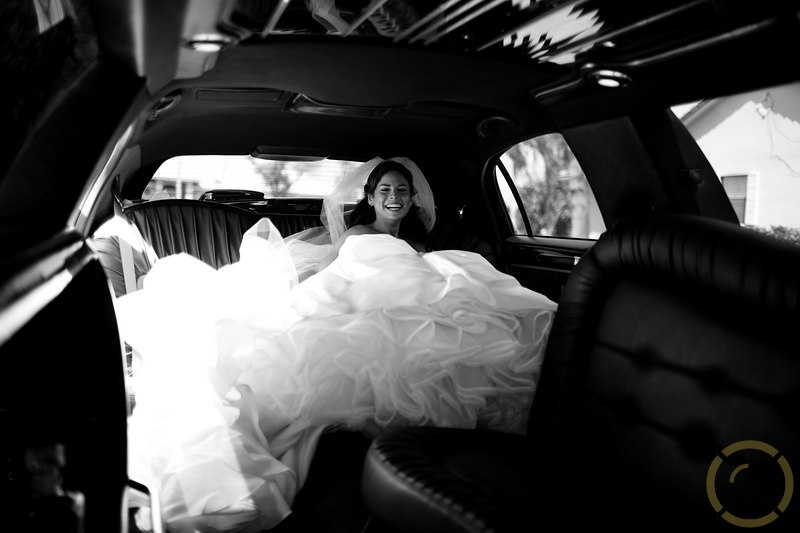 This bride in her princess wedding dress is enjoying the back seat of her elegant limo.