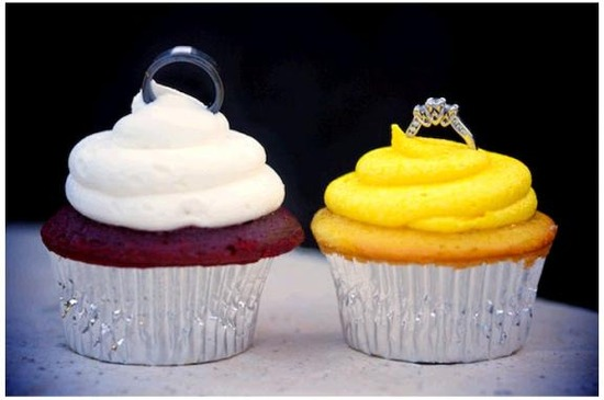 Red devil's food and vanilla cupcakes with white and yellow frosting and wedding rings on top.
