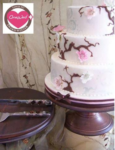 This beautiful three-tiered wedding cake with pink roses is displayed on a brown pedestal
