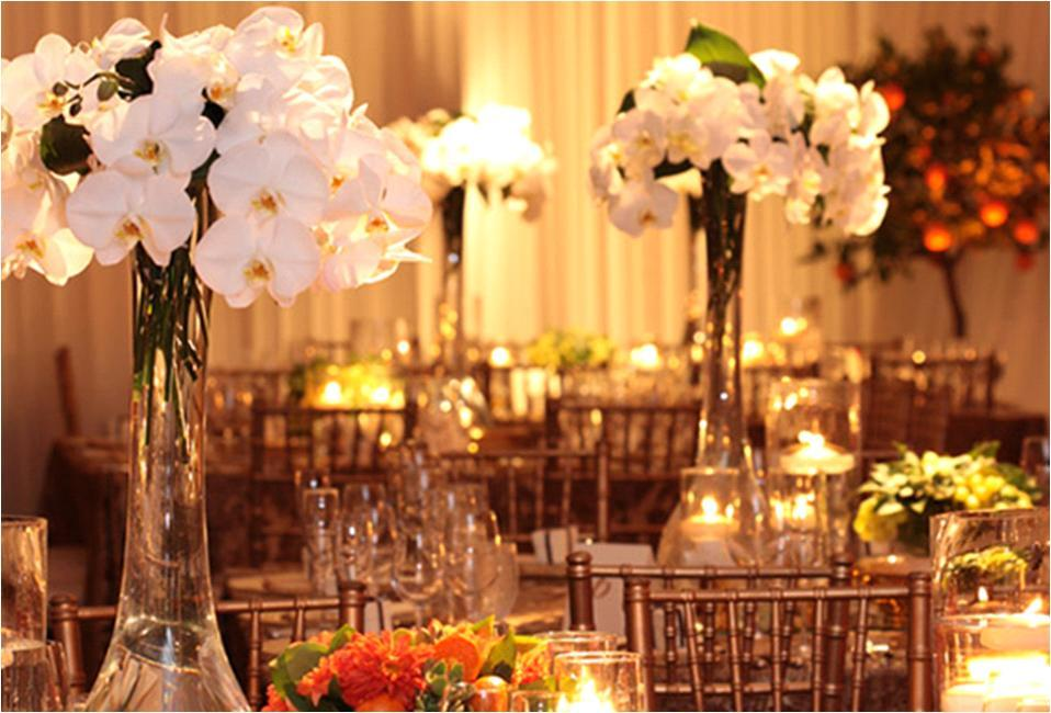 High white orchid table centerpieces accent reception tables; bright orange floral accents add a pop