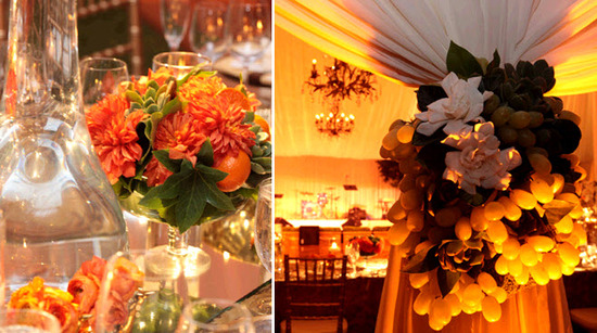 Bright orange flowers with green succulents for table centerpieces; grapes and oranges were used as