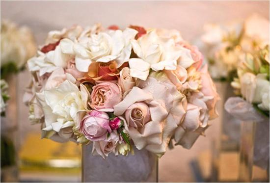 Romantic blush-based low wedding reception centerpiece with white, ivory, soft pink and nude flowers