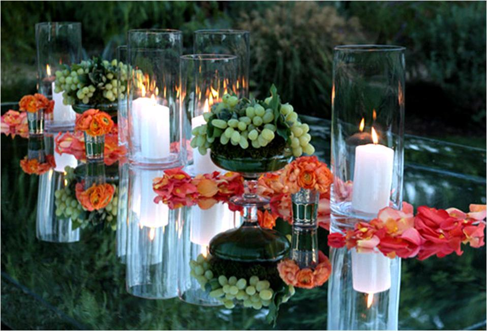 Bright orange and coral rose petals strewn on mirrored reception table; accented with green grapes a