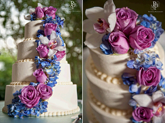 Ivory four-tier stacked wedding cake adorned with fuchsia roses and purple-blue hydrangeas