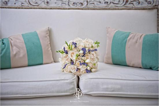 Bride's ivory and deep violet bridal bouquet sits on white couch