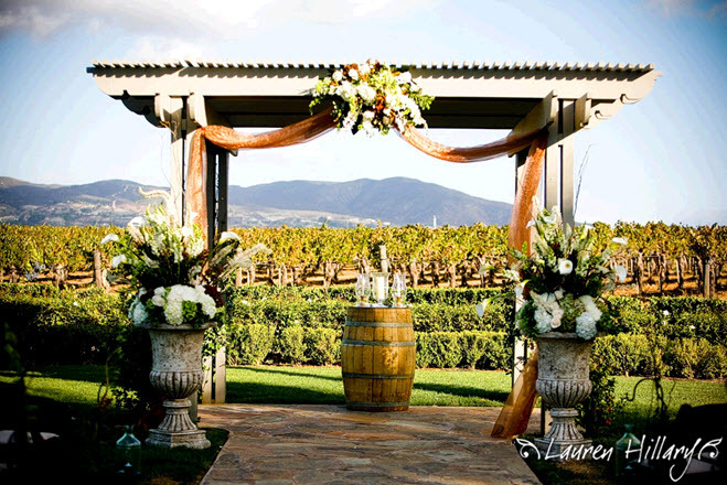 Outdoor-wedding-ceremony-at-winery-mountains-in-background-wedding-arbor.full