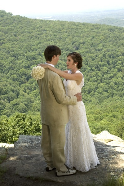 This casual bride and groom are standing on a mountain top . The bride wears a traditional white dre
