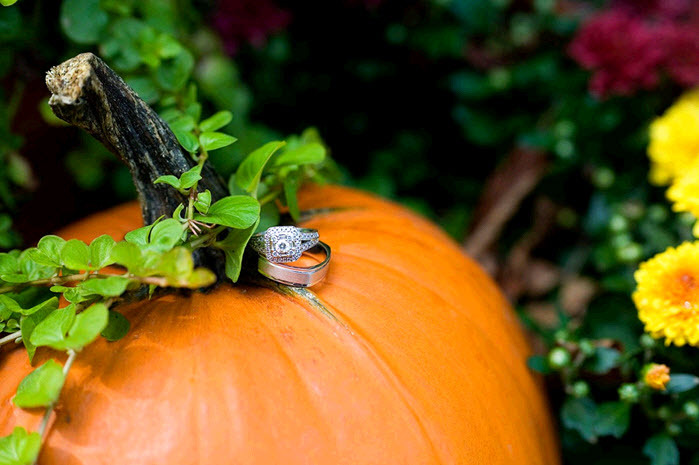 Diamond-cushion-cut-engagement-ring-and-platinum-wedding-band-sit-atop-orange-pumpkin-fall-outdoor-rustic-mn-wedding.full