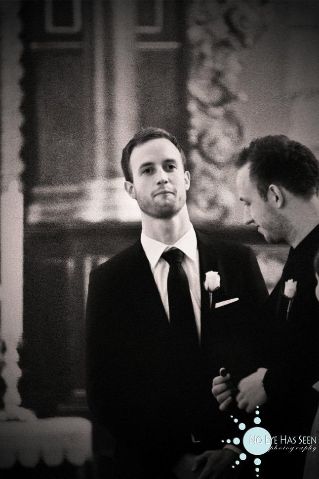 The groom at the wedding ceremony, in a black formal tux, when he sees his beautiful bride for the f