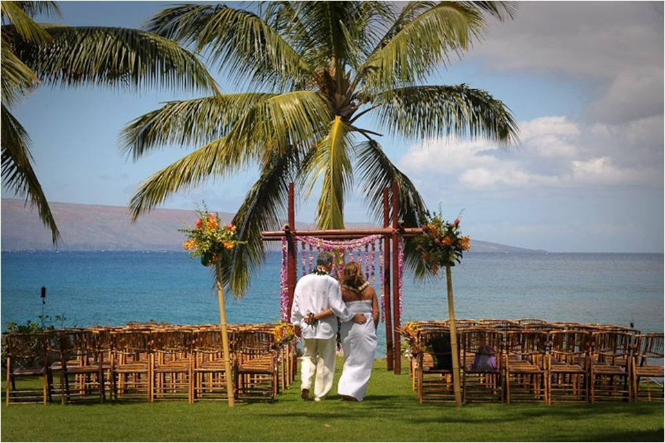 Casual-beach-bride-and-groom-walk-together-to-tropical-floral-arbor-oceanside-pink-orange-green-flowers.full