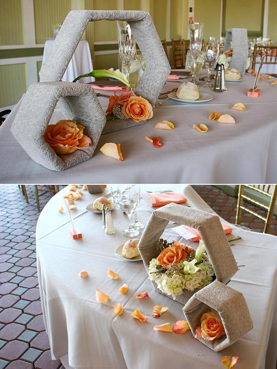 Hexagon wooden pieces wrapped in a gray velvet fabric and decorated with hand-picked peach roses and white calla lilies for the newly wed's dinner table