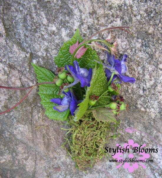This purple, pink, and green boutonniere is decorated with grapevines and moss.
