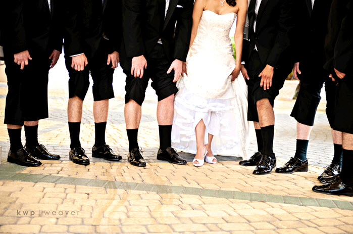 Fun-wedding-photo-groomsmen-show-off-black-tux-socks-shoes-bride-lifts-wedding-dress-to-show-off-bridal-heels.original