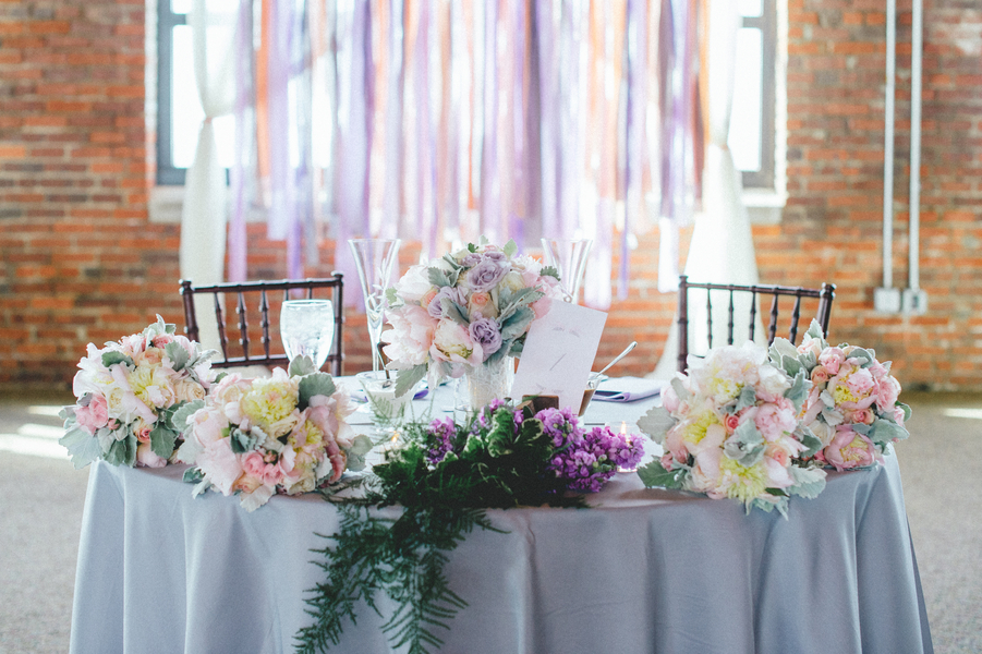 Pretty bride and groom reception table with pastel flowers onewed