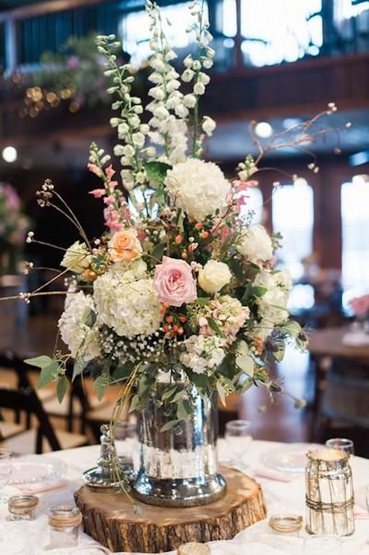 Gorgeous floral centerpiece on a rustic wood slab for Floral arrangements for wedding reception centerpieces