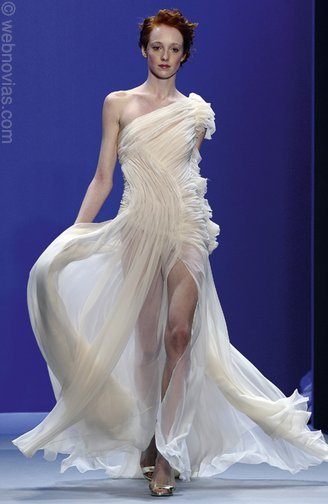 This haute couture wedding dress features an assymetrical neckline and a flowing skirt.