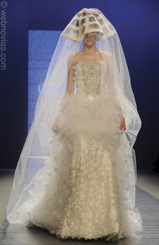 This extreme wedding dress features a hat and a full body veil as well as a feathery poof around the