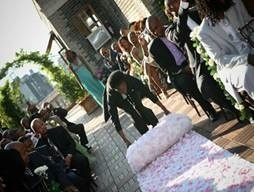 This carpet of artificial flowers is being rolled out by a helpful groomsman in a dark suit.