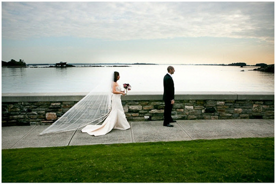 Bride and groom face away from one another by lake before first look