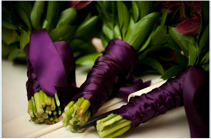 Wedding-detail-shot-romantic-bridal-bouquet-and-bridesmaids-flowers-tied-with-eggplant-purple-satin-ribbon.full