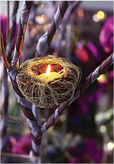 Faux bird's nest with white votive candle, placed in branches covered with purple satin ribbon