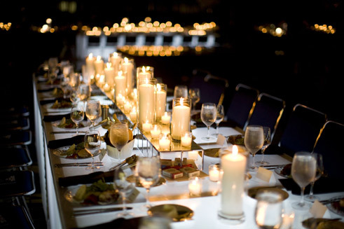 Long wedding reception table covered in white votive candles placed on mirrored pedestals