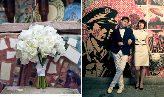 White bridal bouquet made with white peonies; bride and groom pose in front of colorful mural