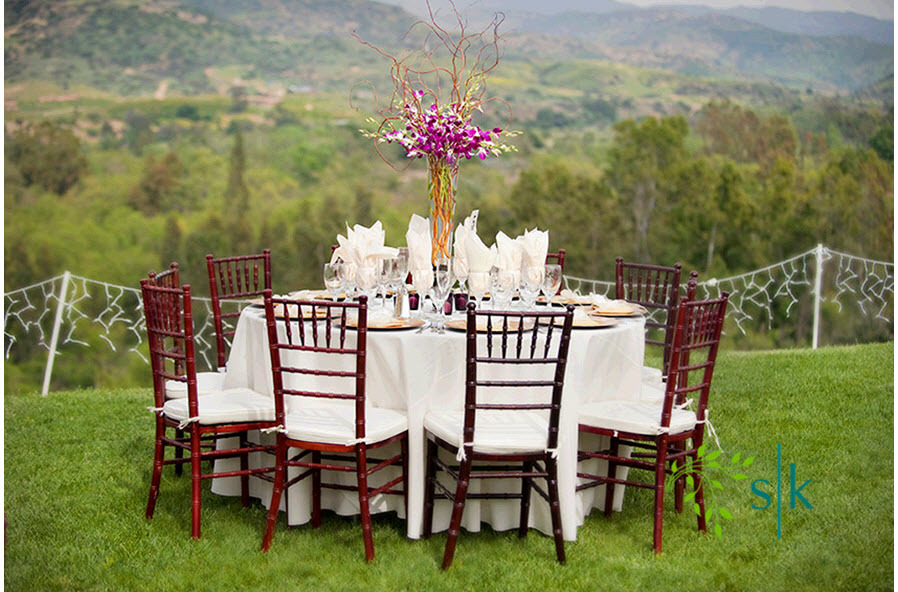 Casual Round Wedding Reception Table With High Purple Orchid Centerpiece Sits Atop Orange County Rol