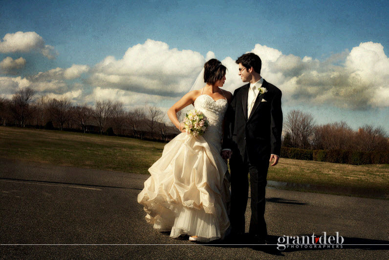 Bride In Ivory Ballgown Dramatic Wedding Dress Poses With Groom Outside