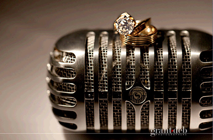 Artistic-wedding-detail-shot-gold-wedding-bands-diamond-engagement-ring-sit-atop-vintage-microphone.full