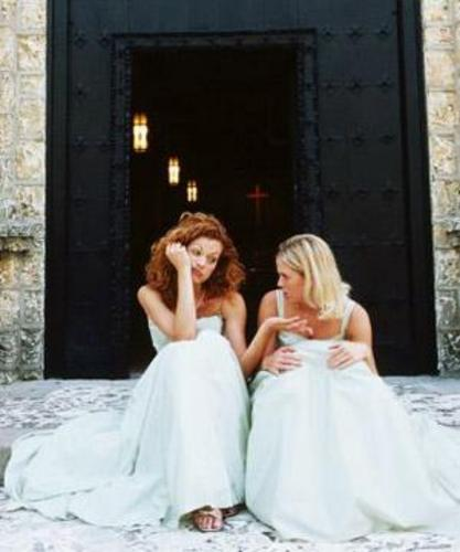 This blonde bride vents to her bridesmaid on the steps of the church. Bridesmaid and bride stress is