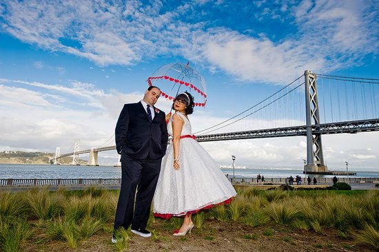 Retro bride and groom pose outside in front of San Fran golden gate bridge