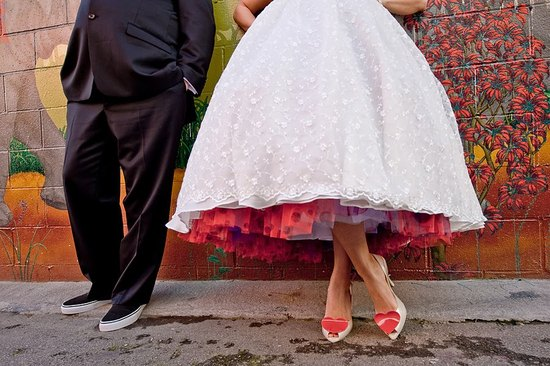 Bride wears tea-length white wedding dress with red, purple polka dot tulle petticoat underneath!