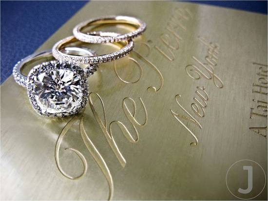 The bride's beautiful diamond engagement ring and wedding ring sit atop her gold letterpress wedding