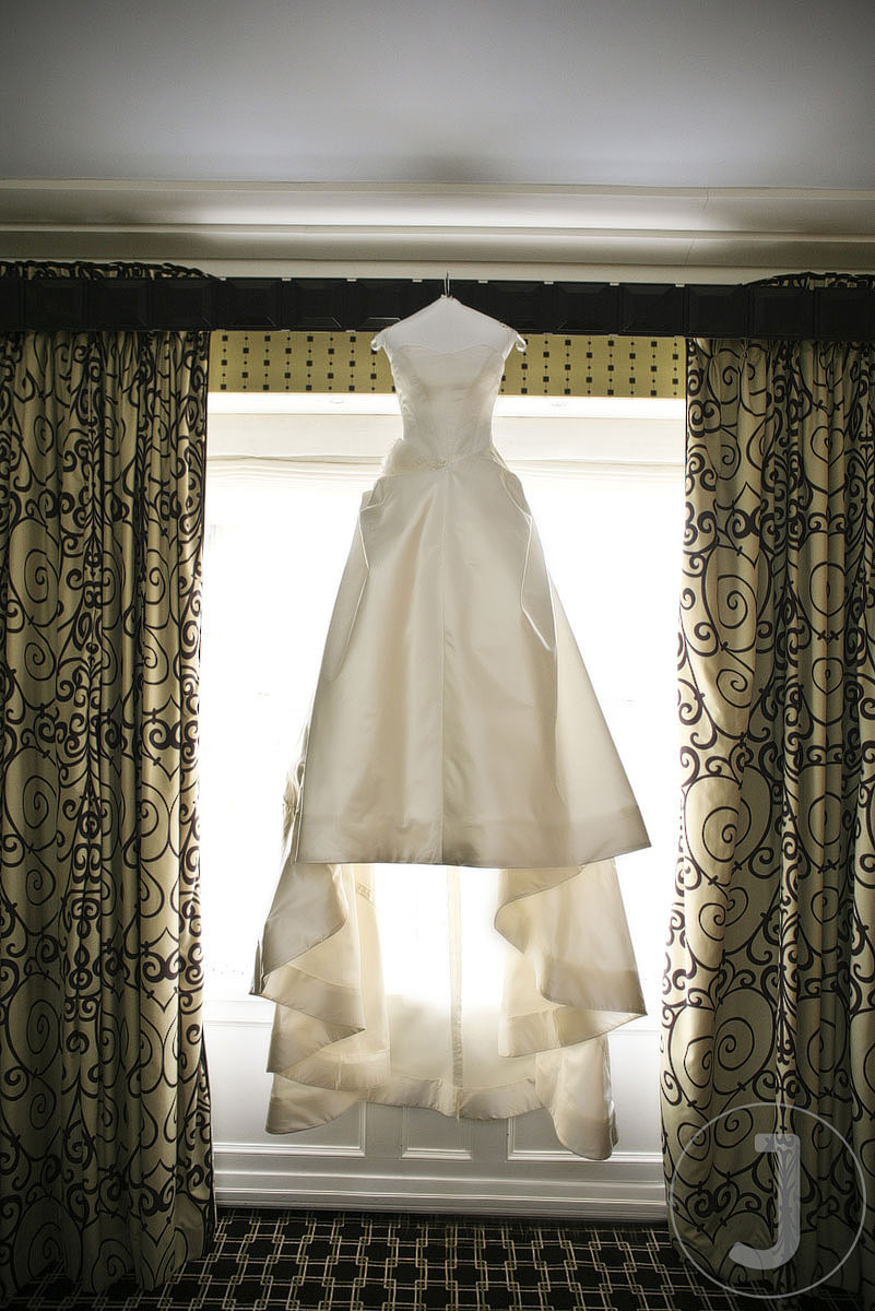 The bride's beautiful Vera Wang ivory wedding dress hangs in the window of her New York City hotel r