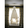 Ivory-couture-wedding-dress-hangs-in-window-of-luxe-new-york-city-wedding-venue.square