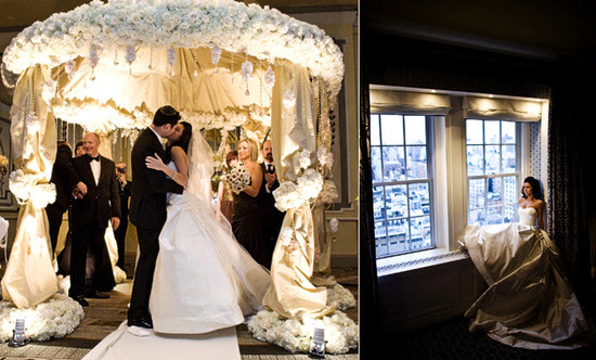 The bride and groom kiss under an ornate ivory chuppah. The bride is wearing a stunning Vera Wang st