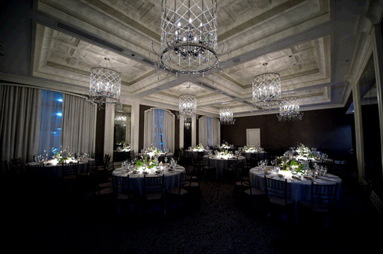 Stunning wedding reception room with sparkling chandeliers and round tablescapes