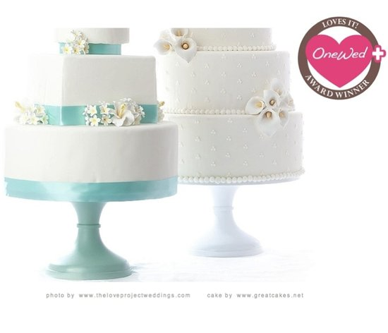 These beautiful white three-tiered wedding cakes are displayed on cake stands from Sarah's Stands.