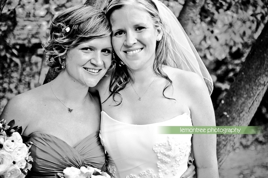 Bride in white strapless wedding dress poses with her loving sister
