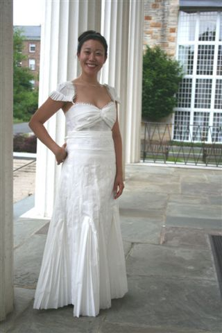This bride is wearing a sweetheart neckline white wedding dress with capped sleeves. The white weddi
