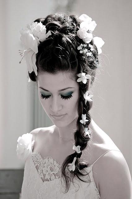 Gorgeous bridal hairstyle with long braid sprinkled with white flowers