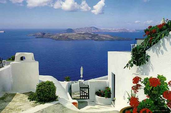 Stunning romantic view from white wash villa in Santorini- deep blue sea bright red flowers